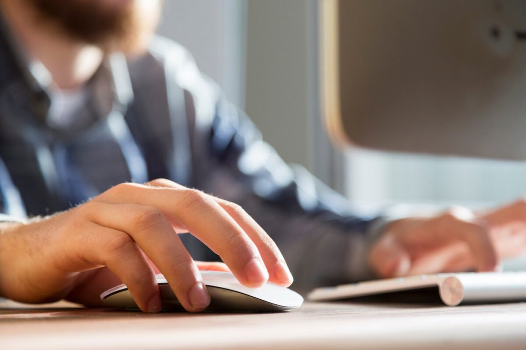 person sitting at desk with one hand on the mouse and the other hand on the keyboard